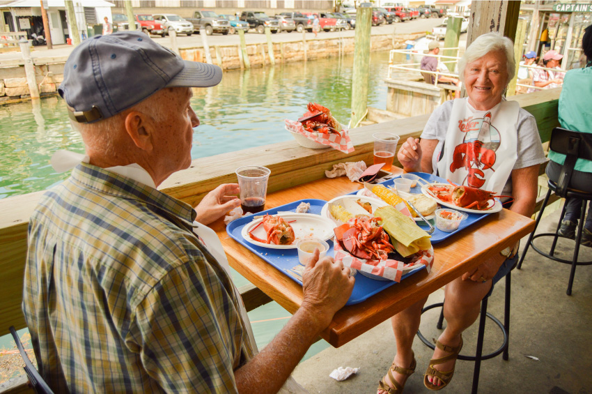 Our Story - Couple enjoying a lobster dinner at Beal's